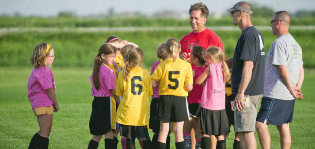 A group of girls and coaches on a soccer field